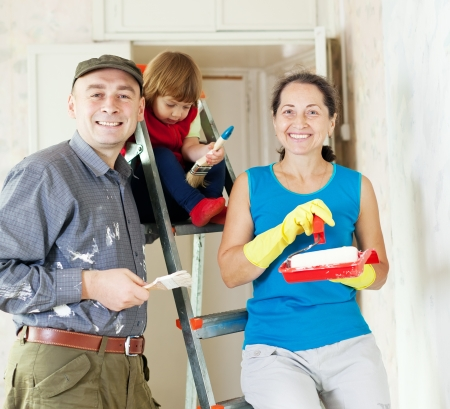 Happy family of three makes makes repairs in the apartment together photo