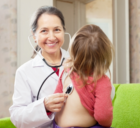 children's doctor: friendly mature pediatrician doctor examining 2 years baby with  stethoscope. Focus on woman