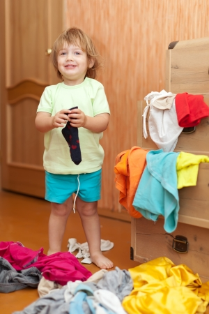 scallywag:  Baby girl  chooses dress in parents wardrobe  Stock Photo