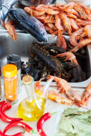 nutricion: Heap of fresh uncooked seafood and  spices in domestic kitchen  Stock Photo