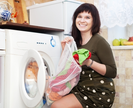 Happy young housewife doing laundry at her home photo