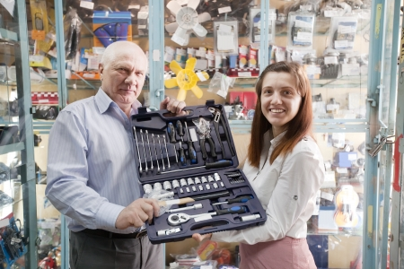 mature man and woman holds  automotive  correction tool set in  auto parts store photo