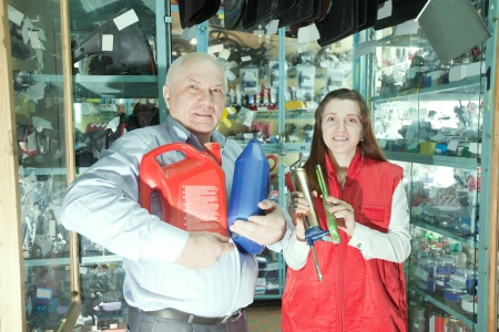 motor oil: Mature man buys motor oil in auto parts store