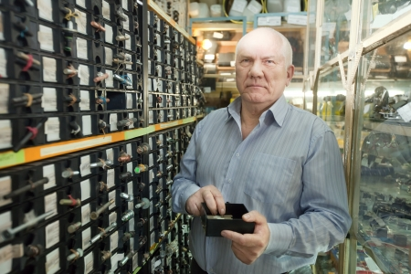 mature man chooses fasteners in  auto parts store photo