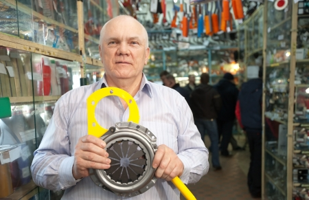 mature man holds  engine clutch  in  auto parts store Stock Photo - 20910759