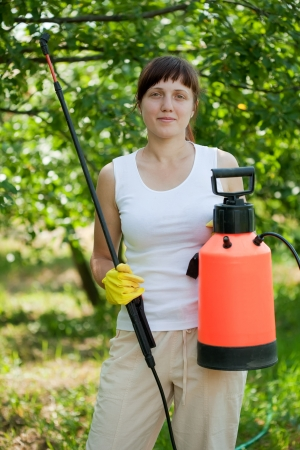 Woman holding  garden spray  in the yard photo
