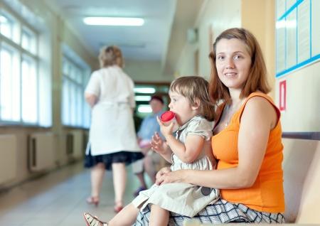urinalysis: donna con bambino con il campione delle urine presso la clinica