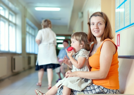 urinalysis:  woman with child with urinalysis sample at the clinic