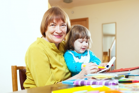 Happy mature woman and child drawing with colored pencils together at table photo