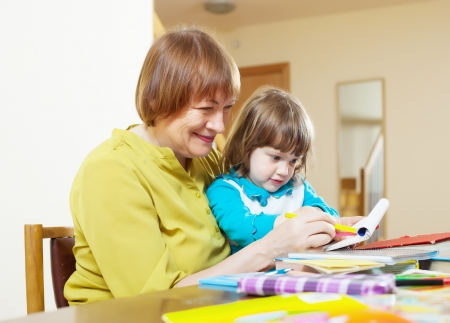 Happy grandmother and child drawing with colored pencils together at table photo