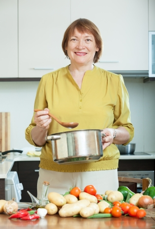 Smiling mature woman cooking  vegetarian lunch in domestic kitchen photo