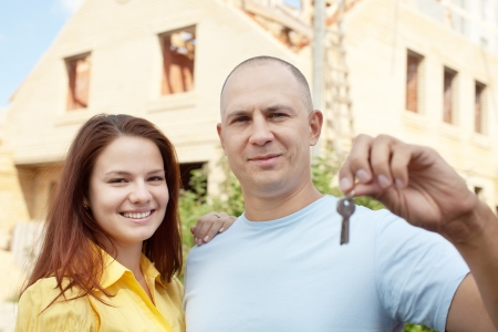 Happy couple with key against building new brick house    photo