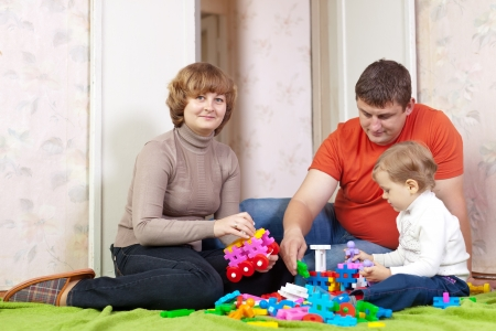 Happy parents and child plays with meccano set in home photo