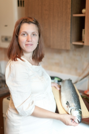 gravida: pregnant woman with salmon in the kitchen