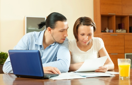 parsimony: serious couple woman reading document at home Stock Photo