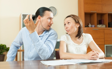 Adult man and woman having quarrel about documents at home photo