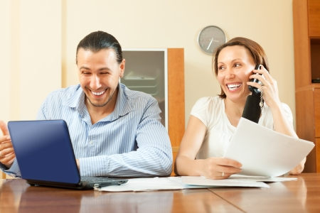 Cheerful  couple looking financial document at home photo