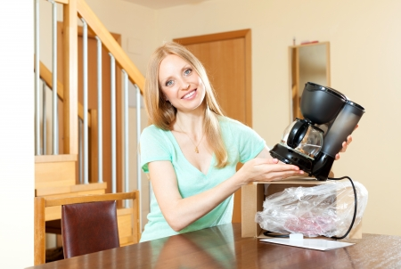 coffeemaker: Young woman unpacking and reading manual for new coffeemaker at home interior Stock Photo