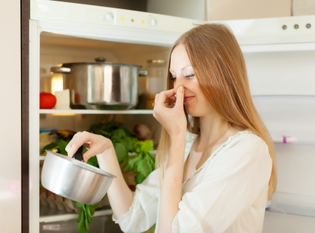 frowy: Long-haired  woman  holding her nose because of bad smell near fridge at home