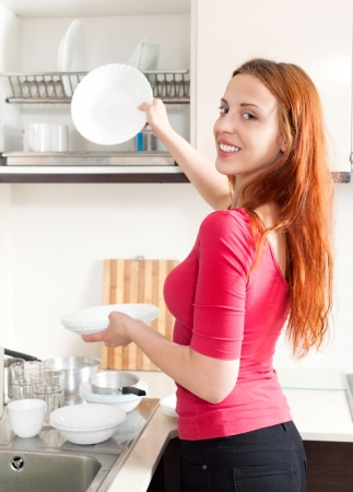 Happy cute red haired girl washing plates in home kitchen photo