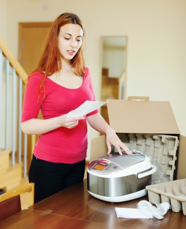 slow cooker:  woman  reading guarantee card for new multicooker  at home interior