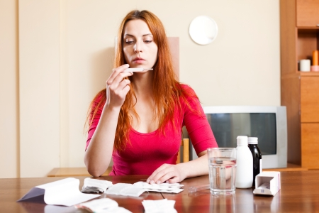 troche: Sick young red-haired woman looks by thermometer at home Stock Photo