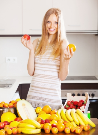 exuberance: Positive blonde long-haired woman with heap of ripe fruits in home kitchen  Stock Photo