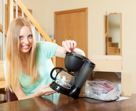 coffeemaker: Woman with new electric coffee maker at home in living room