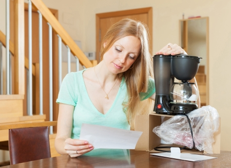 Happy young woman with new coffee machine at home photo