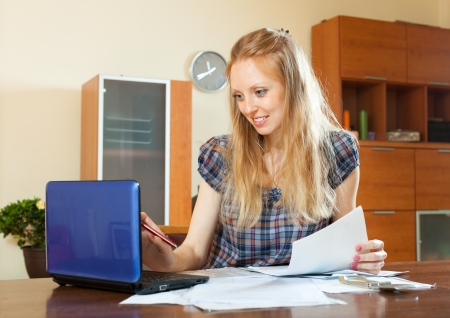 Positive long-haired woman working with financial documents and laptop at home interior photo