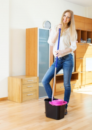 ordinary woman: Cheeful ordinary woman washing parquet floor with mop in living room