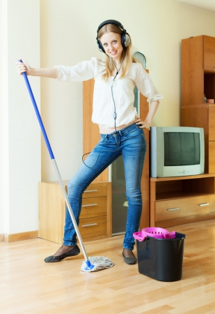 woman in headphones washing floor with mop in living room photo