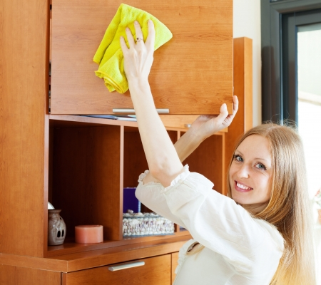 clean house: young woman cleaning furniture at home
