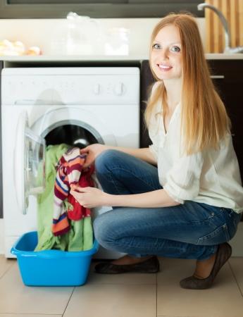 lavadora con ropa: Mujer rubia sonriente que pone la ropa para lavadora