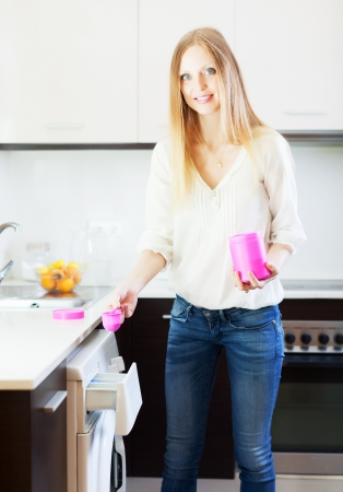 Happy blonde  woman doing laundry with detergent at home Banco de Imagens