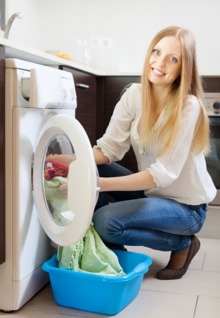 Happy blonde woman loading clothes into the washing machine  at home photo