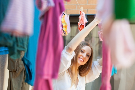 Smiling woman hanging clothes to dry on clothes-line  after laundry photo