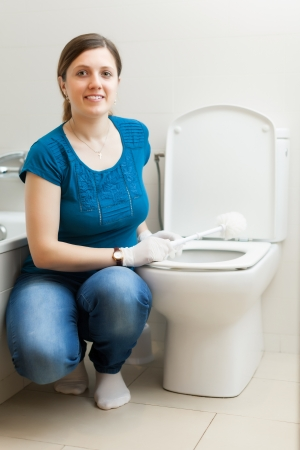 Smiling housewife cleaning toilet bowl with brush Stock Photo - 21111041