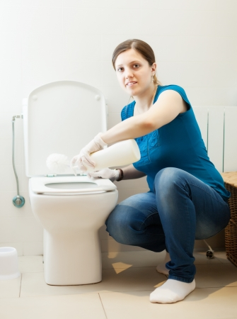 woman cleaning toilet bowl with brush and cleaner at her home Stock Photo - 21111045