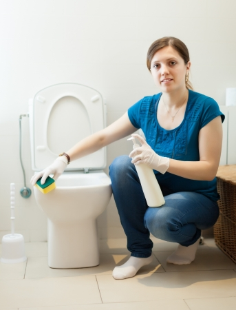 Smiling housewife cleaning toilet with sponge and cleaner at her home photo