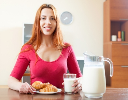 Young woman having breakfast with milk in morning at home interior  photo