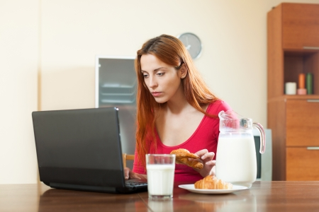 Girl reading e-mail in laptop during breakfast time at home photo