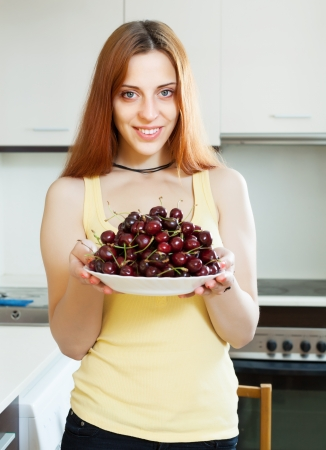 Smiling  girl holding plate with cherries at home kitchen photo
