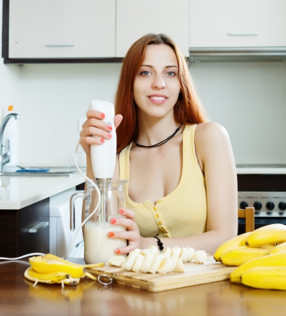Young woman making beverages with blender from bananas and milk at domestic kitchen  photo