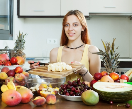 Positive long-haired woman making fruit salad with banana in home kitchen  photo