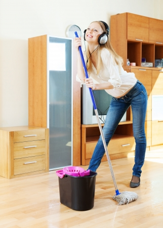 cheerful girl in headphones washing floor with mop in living room photo