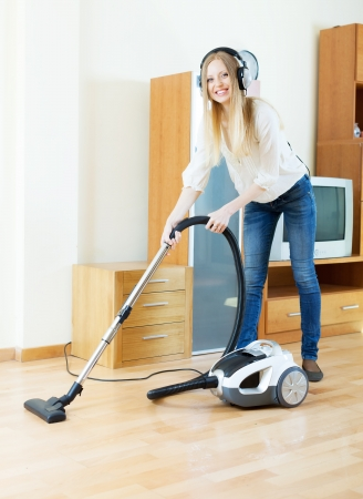 cheerful blonde woman in headphones cleaning with vacuum cleaner on parquet floor photo