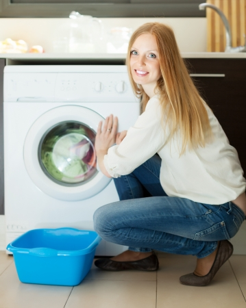 Home laundry. Blonde long-haired woman using washing machine at home Stock Photo - 21198961
