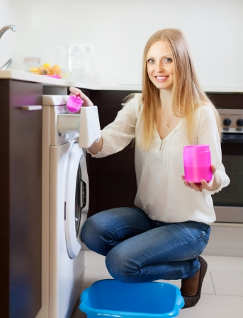 Happy woman doing laundry with detergent at home Banco de Imagens