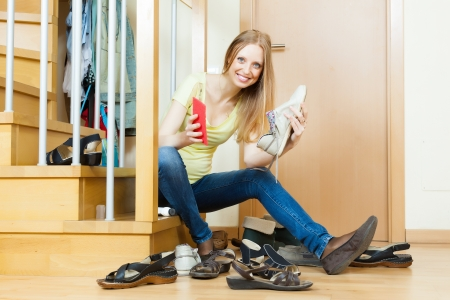 Happy woman sitting on stairs and cleaning footwear photo